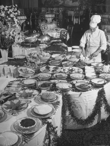 chef-preparing-dish-at-buffet-table-in-dining-room-of-the-waldorf-astoria-hotel